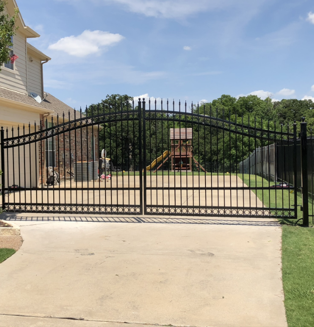 large arched top metal gate at a home in Fort Worth